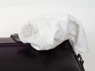Nach Wischen über der Oberfläche einer Ledertasche zeigt ein weißes Tuch Spuren der Taschenfarbe.