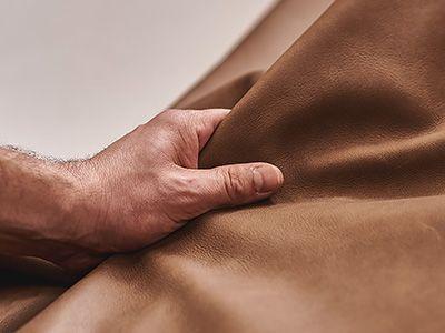 Hand und atmungsaktives braunes Leder