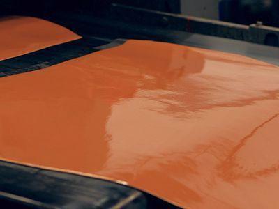 Bei beschichtetem Leder wird auf das Leder eine mehr als 0,15 mm dicke Schicht aus Farbe oder einer Deckfolie aufgetragen.