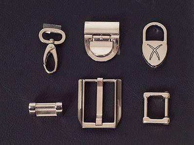 Schlösser, Karabinerhaken, Schnallen und Ringe aus Metall werden als Beschlag einer Tasche bezeichnet.