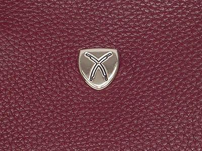 Das Metallemblem zeigt zwei Scherdegen als Markenzeichen. Befestigt wird es mit Klammern auf der Vorderseite der Tasche.