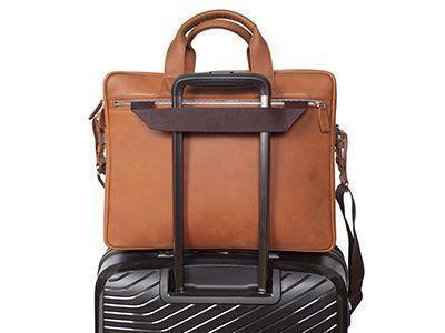 Das Anbringen einer Tasche mit einem Gurt auf einem Rollenkoffer erlaubt eine bequeme Beförderung.